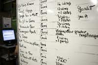 A dry-erase board shows the day's printing schedule.