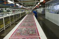 """A continuous 160-meter stretch of silk twill will be cut and hand-hemmed into $60,000 worth of brightly colored scarves in the popular design """"Au Fil du Carré."""""""