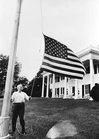 H.L. Hunt personally raises and lowers the flag in front of his Dallas home, a replica of Washington's Mount Vernon, which sits on 10 acres of land along White Rock Lake and which Hunt bought during the depression for a bargain price of $67,000.