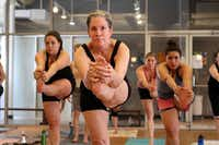 "Patty Baio in a ""standing head to knee"" pose during a heated yoga class at Bikram Yoga Dallas, on March 16, 2012 in Dallas."