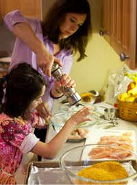 Samantha McKenzie gets cooking help from daughter Bella, who is working on Crunchy Chicken  Fingers with Tangy Dipping Sauce.