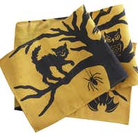 Enchanted forest Black cats, owls and bats on a hand-printed, jute table runner are ready to cast a hex on visitors to their forested world. The Sleepy Hollow table runner is 94.5 inches long. $14.95 on sale at wisteria.com