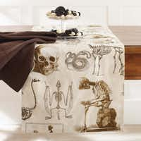 Remains of the day Skeletons of humans, reptiles and animals abound on a printed, cotton toile table runner making Halloween dining subtly creepy. 108 inches long, $49.95, set of four napkins $29.95 at Williams-Sonoma, multiple locations, and williams-sonoma.com