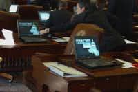 In a frame grab from video, Texas State Rep. Kelly Hancock District 91 (R-Fort Worth), is captured reaching over to the desk of fellow Republican Rep. Ken Paxton District 70 (R-McKinney) to press the button on Paxton's desk and vote on his behalf, while Paxton was absent when a vote was called during Texas House proceedings on Wednesday.