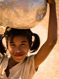 A happy young girl carrying water in Mrauk U, Myanmar.Jonathan Look Jr.  -  Special Contributor