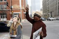 Lacey Gardner (front) and Chelsey Healy listen as Ron Washington points out the window on the sixth floor of the former Texas School Book Depository building and describes a JFK conspiracy booklet he sells.
