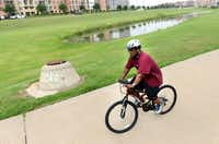 Andre Herron, who lives in the Las Colinas Urban Center, rides his bike along the trails in the neighborhood, which was rated the healthiest place to live in Irving and Coppell.