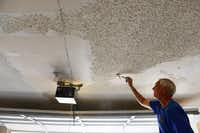 Plain-O Helpers founder Fred Clark scrapes the ceiling of a Plano resident's garage. The seniors helping seniors Christian-based group helps local Plano residents with minor home maintenance and repairs.