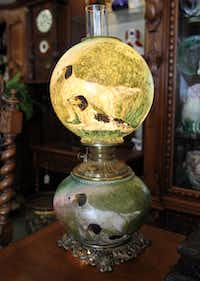 A lamp depicting dogs and birds, from the late 1880s
