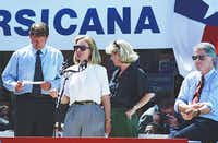 Democratic presidential candidate Bill Clinton, right, rolls up his sleeves as his wife Hillary Clinton makes a short speech during a campaign stop in Corsicana, Texas on August 28, 1992. They were joined by running mate Al Gore and his wife Tipper. (David Woo/The Dallas Morning News)