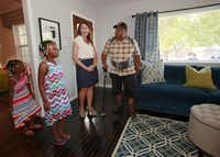 Lisa Robison, founder and president of Dwell with Dignity, shows of the newly remodeled home for single dad and Marine veteran Ben Anderson (right) and his daughter, Anaijah McQueen, 7 (left), as they enter the living room of the home. Iquana McQueen (far left), 4, is Anijah's half-sister. The home was remodeled by the organization partnership of Dwell with Dignity and Rebuilding Together Greater Dallas.( Ben Torres  -  Special Contributor )
