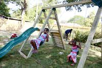 Anaijah McQueen (left), 7, with her sister, Iquana McQueen, 4, play on a swing and slide playground in the backyard of Anaijah's family's newly remodeled home. The home was remodeled by the organization partnership of Dwell with Dignity and Rebuilding Together Greater Dallas.( Photo by BEN TORRES    -  special contributor )