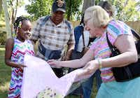 Single dad and Marine veteran Ben Anderson (center) stands with his daughter, Anaijah McQueen (left), 7, as she receives a homemade quilt for her bed from Cheryl Phillips of Flower Mound, as the family tour the inside and backyard of their newly remodeled home in South Dallas. Phillips read about the family in The Dallas Morning News and decided to donate two homemade quilts for Anderson and his daughter.( Photo by BEN TORRES    -  special contributor )