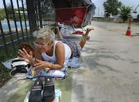 Julie Garcia said she hangs out on the sidewalk near the Austin Street Shelter because she was kicked out of a homeless shelter and is out of work.