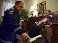 Jack Sides, EMS captain for Plano Fire-Rescue, took patient Carole Young's blood pressure during a recent house call. The paramedics have access to her medical records and can relay information to the hospital and her physician and perhaps help prevent an emergency call.( Rose Baca  -  Staff Photographer )
