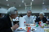 Phan Minh, Fr. Hoc Ngyuen and Deacon Hung Uong enjoy the feast after Mass. Fr. Hoc Ngyuen was visiting the church from Vietnam.