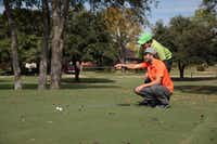 <TypographyTag1>Lucas Moffitt</TypographyTag1> (kneeling) and his father Rick discuss Lucas' upcoming putt during a two-man <252>scramble at Duck <252>Creek Golf Club.(Staff photo by CHRIS DERRETT)