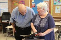 Bertucci flips through Bishop Lynch yearbook pages with her husband, Jim.Staff photo by CHRIS DERRETT