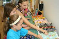 Elise Little, (front) Shannah Roberts and Erin McElhone choose fabrics during a summer sewing camp at Urban Spools.
