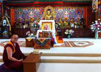 A monk sits before the altar in the shrine room of the Tibetan Mongolian Buddhist Cultural Center in Bloomington, Ind.