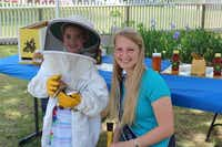 Pettibon, right, serves as a spokeswoman for the honeybee industry and gives regular talks to school and community groups. Above,she helps a young beekeeper at Nash Farm in Grapevine.(Photo submitted by CHRISTIE PETTIBON)