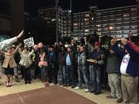 """A crowd gathered outside the Dallas Jack Evans Police Headquarters on Sunday, November 22, 2015, sings """"We Shall Overcome"""" during a rally after a spate of attacks and robberies in the Oak Lawn neighborhood. (Claire Cardona/Staff writer)"""