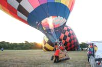 "Luc and Loren Goethals finish inflating ""Zipper,"" their hot air balloon. Luc took two passengers up in the air above McKinney for an hour's flight on Sept. 8."