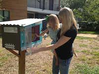 Kimberly Vowell (right) and daughter Reagan, 3, look over the books in their Little Free Library in Little Forest Hills.