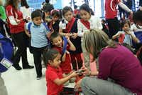 F.M. Gilbert Elementary principal Patty Gustamante looks through a donated backpack along with several students. The backpacks, filled with school supplies, were donated by #40AOK, a group of friends who joined together to promote global acts of kindness.(Staff photo by MEREDITH SHAMBURGER - neighborsgo)