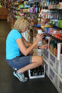 Nicole Meadows restocks some of the store's hundreds of soda offerings.