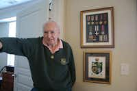 Lake Highlands resident Dennis King stands next to a case displaying medals from his service as a squadron tank commander in the British Army during World War II. Among King's honors is the Military Cross (middle row center).(Staff photo by HEATHER NOEL - neighborsgo)
