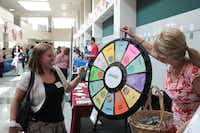 Tisha Weiss (left) spins a prize wheel at Richardson ISD's new teacher welcome fair at Berkner High school. Weiss will teach second grade students at Forest Lane Academy.