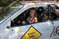 """Olivia Leonard sits behind the wheel of """"Baby on Board,"""" a car the Leonard family races in the 24 Hours of Lemons, a 24-hour endurance racing circuit for $500 cars. Olivia, 16, will join the driving rotation with her father, John, and mother, Michelle, in their next race on Sept. 28 at Texas Motor Speedway."""