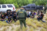 Immigrants suspected of being in the country illegally sit in a group after U.S. Border Patrol agents detained at least 80  immigrants who'd been living in a makeshift encampment in suburban McAllen on April 17. The immigrants told authorities they had been at the site in McAllen for at least a week with little food or water. Tents and huts were camouflaged with mesquite branches and they slept on pieces of cardboard on the ground.(Gabe Hernandez - McAllen Monitor)