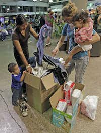 Women and children look through a box of cloths that were donated by volunteers at the Greyhound bus terminal, Thursday, May 29, 2014 in Phoenix.  About 400 mostly Central American women and children caught crossing from Mexico into south Texas were flown to Arizona this weekend after border agents there ran out of space and resources.  Officials then dropped hundreds of them off at Phoenix and Tucson Greyhound stations, overwhelming the stations and humanitarian groups who were trying to help. (AP Photo/Rick Scuteri)Rick Scuteri - AP