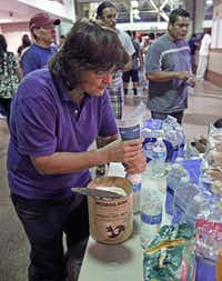Volunteer nurse Ronda Kelso, of Phoenix, mixes powder milk for immigrants waiting at at the Greyhound bus terminal, Thursday, May 29, 2014 in Phoenix. About 400 mostly Central American women and children caught crossing from Mexico into south Texas were flown to Arizona this weekend after border agents there ran out of space and resources.  Officials then dropped hundreds of them off at Phoenix and Tucson Greyhound stations, overwhelming the stations and humanitarian groups who were trying to help. (AP Photo/Rick Scuteri)Rick Scuteri - AP
