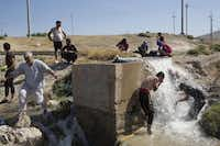 Yazidis bathe by a roadside in northern Iraq. Between 50,000 and 150,000 members of the religious minority are trapped in the mountains, British officials said.Adam Ferguson  -  The New York Times