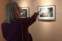 Sandy Faltermeier of Dallas points at one of Terry Cockerham photographs at the Irving Arts Center.(Gregory Castillo - Staff Photographer)