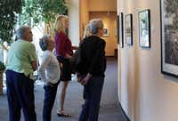 A group of visitors from the Campbell Green Recreation Center look through a gallery of Terry Cockerham's photographs at the Irving Arts Center.(Gregory Castillo - Staff Photographer)