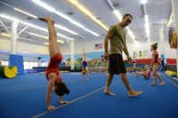 Coach Eduoard Iarov walks past McCauley Harrington, 8, as she does a hand stand during an afternoon practice at Iarov Elite Gymnastics in Dallas .(Rose Baca - neighborsgo staff photographer)
