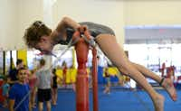 Savannah McDonald, 8, trains on the uneven bar during an afternoon practice. In January, Iarov launched a more competitive program alongside the gym's regular classes.(Rose Baca - neighborsgo staff photographer)