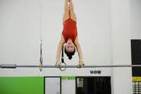 McCauley Harrington, 8, trains on the uneven bars.(Rose Baca - neighborsgo staff photographer)