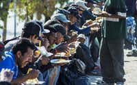 Homeless people in Tijuana, Mexico, many of them deportees, eat a church-provided meal. Many of those repatriated last year from the U.S. re-entered through Tijuana.( Omar Torres  - Press )