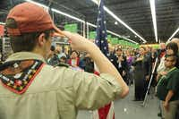 Chris Freeland of Boy Scout Troop 100 salutes the American flag during the grand opening of the Walmart Neighborhood Market in Garland at Miller Road and Garland Avenue.Photo submitted by STEVE WALKER