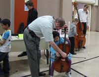 Neil Ferguson helps a young cellist during a past symphony event.( Photo submitted by NANCY WRIGHT )