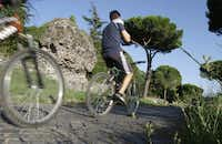 In this Sept. 7, 2013 photo, people cycle past ruins along the Appia Antica, the ancient Roman Appian Way, in Rome. The Ancient Appian Way was built in the fourth century B.C. by the censor Appius Claudius as a road to connect Rome with southern Italy.