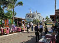 Street vendors sell souvenirs near Royal Caribbean's Allure of the Seas in Falmouth, Jamaica. If you're traveling with a large family, consider skipping the shore excursions in favor of exploring on your own.