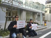 Bitcoin trader Kolin Burges, right, of London and American Aaron (only his first name was given) hold protest signs as they conduct a sit-in in front of the office tower housing Mt. Gox in Tokyo Tuesday, Feb. 25, 2014. The website of major Bitcoin exchange Mt. Gox is offline Tuesday amid reports it suffered a debilitating theft, a new setback for efforts to gain legitimacy for the virtual currency. The URL of Tokyo-based Mt. Gox was returning a blank page. The disappearance of the site follows the resignation Sunday of Mt. Gox CEO Mark Karpeles from the board of the Bitcoin Foundation, a group seeking legitimacy for the currency. Burgess said he had picketed the building since Feb. 14 after flying in from London, hoping to get back $320,000 he has tied up with Mt Gox. (AP Photo/Kaori Hitomi)Kaori HItomi - AP