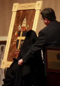 Chancellor of The Catholic Diocese of Lubbock Marty Martin unveils the coat of arms of Pope John Paul II at the Overton Hotel and Conference Center during an announcement of an exhibit displaying artifacts from Pope John Paul the II is coming to Lubbock, Thursday, Nov. 29, 2012. The coat of arms is inlay wood made from 21 different types of wood. Over 130 items are expected to be on display between March 15, 2013 and May 31, 2013 at The Catholic Renewal Center of the Diocese of Lubbock. (AP Photo/Lubbock Avalanche-Journal, Stephen Spillman)Stephen Spillman - AP