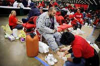 Joe Chavera (left) waited as volunteer Sheila Etonga washed his feet during Saturday's Christmas Gift for the Homeless event in downtown Dallas. The event, in its 11th year, provides goods and services to thousands of people and families.(G.J. McCarthy - Staff Photographer)